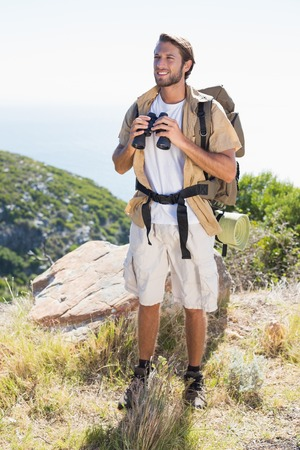 Handsome hiker holding binoculars on mountain trail on a sunny day photo
