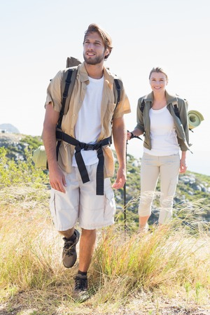 adventuring: Hiking couple walking on mountain trail on a sunny day