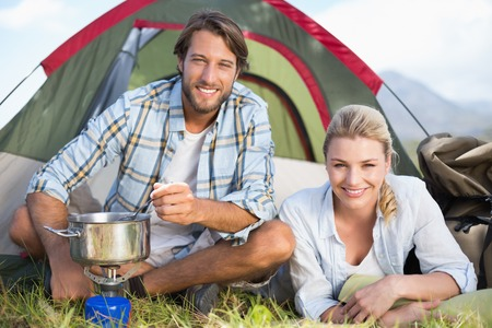 Attractive happy couple cooking on camping stove on a sunny day Stock Photo
