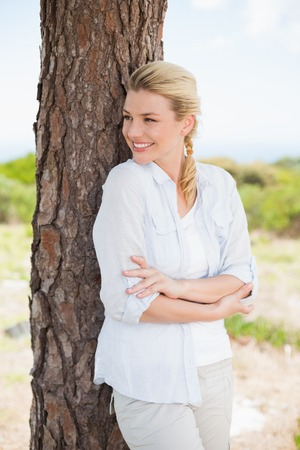 adventuring: Attractive happy blonde standing by tree on a sunny day