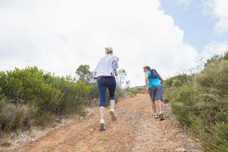 adventuring: Fit attractive couple jogging up mountain trail on a sunny day Stock Photo