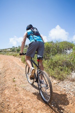 Fit man cycling up mountain trail on a sunny day photo