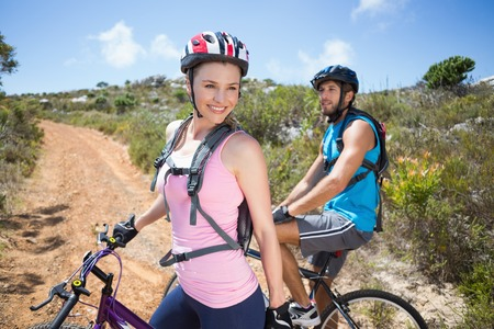 adventuring: Fit couple cycling up mountain trail smiling on a sunny day
