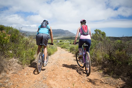 Fit couple cycling on mountain trail on a sunny day photo