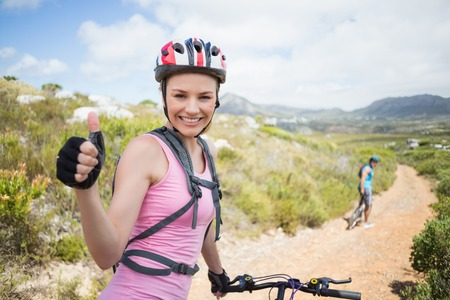 Fit couple cycling on mountain trail woman smiling at camera on a sunny day photo