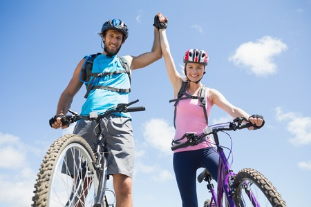 reached: Fit cyclist couple happy to have reached the summit on a sunny day Stock Photo