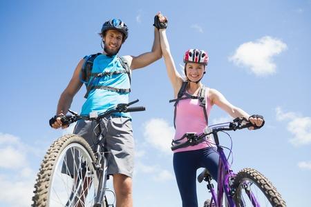 osiągnął: Fit rowerzysta kilka szczęśliwy, że osiągnął szczyt w słoneczny dzień Zdjęcie Seryjne