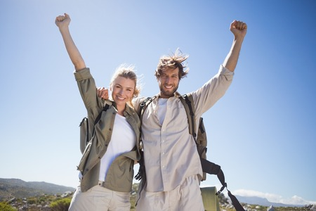 Hiking couple standing on mountain terrain smiling at camera on a sunny day Stock Photo