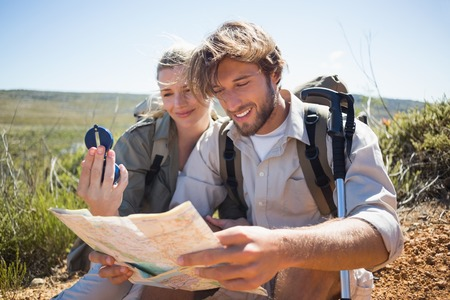 hiking path: Hiking couple taking a break on mountain terrain using map and compass on a sunny day
