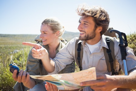 Hiking couple taking a break on mountain terrain using map and compass on a sunny day photo