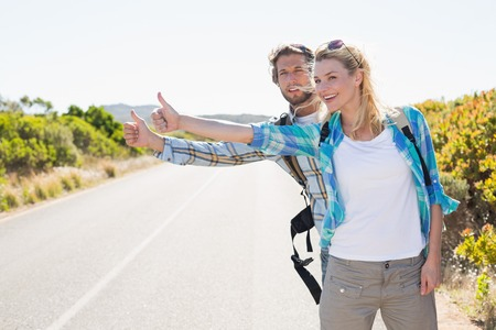 hitch hiker: Attractive couple standing on the road hitch hiking on a sunny day