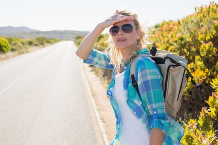 hitch hiker: Attractive blonde hitch hiking on rural road on a sunny day