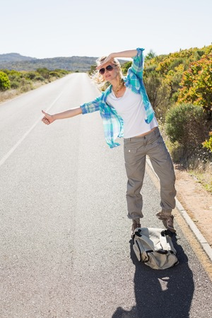Attractive blonde hitch hiking on rural road on a sunny day photo