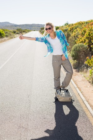 Attractive blonde hitch hiking on rural road on a sunny\ day