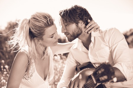 serenading: Handsome man serenading his girlfriend with guitar in sepia tones Stock Photo