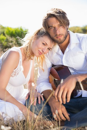 serenading: Handsome man serenading his girlfriend with guitar smiling at camera on a sunny day Stock Photo