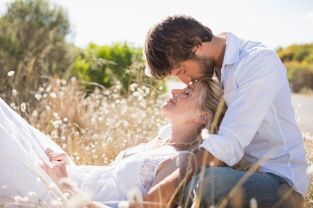 Attractive couple relaxing in the countryside on a sunny day photo