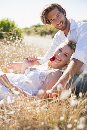 Attractive couple relaxing in the countryside smiling at camera on a sunny day photo