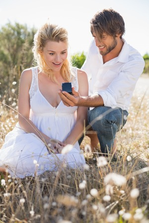 Attractive man proposing to his girlfriend in the country on a sunny day photo