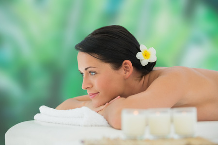 Beautiful brunette relaxing on massage table at a luxury spa photo