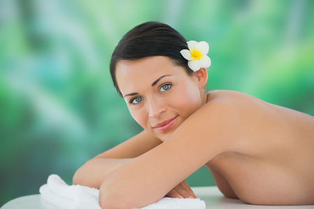 Beautiful brunette relaxing on massage table smiling at camera at a luxury spa photo