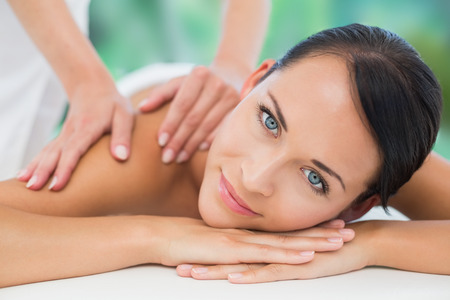hair spa: Beautiful brunette enjoying a back massage smiling at camera at a luxury spa Stock Photo