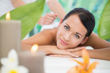 Mooie brunette geniet van een kruiden kompres massage in een luxe spa