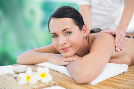 Beautiful brunette enjoying a hot stone massage smiling at camera at a luxury spa photo