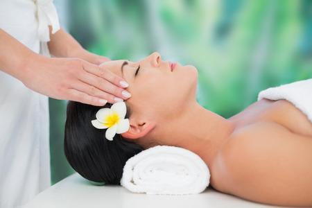 Beautiful brunette enjoying a head massage at a luxury spa photo