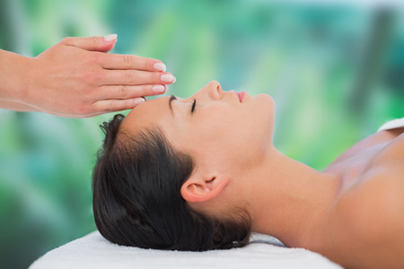relaxing: Beautiful brunette getting reiki therapy at a luxury spa