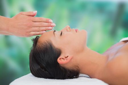 persone relax: Bella bruna ricevendo la terapia reiki in una spa di lusso