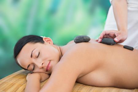 Beautiful brunette enjoying a hot stone massage at a luxury spa photo