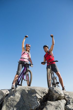 adventuring: Fit cyclist couple cheering at the summit on a sunny day Stock Photo