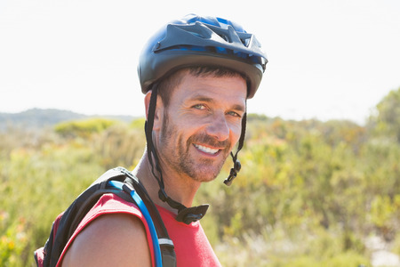 adventuring: Fit cyclist smiling at the camera on country terrain on a sunny day