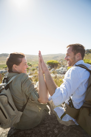 Hiking couple sitting on mountain terrain high fiving on a sunny day photo