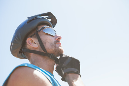 adventuring: Fit cyclist fixing strap on helmet on a sunny day