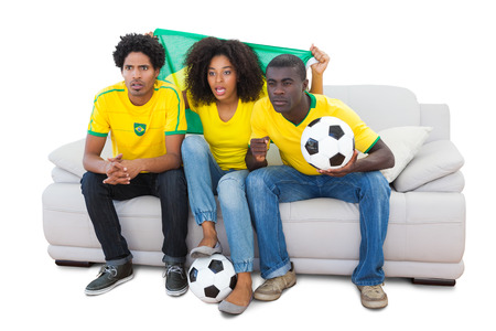 Brazilian football fans in yellow sitting on the sofa on white background photo