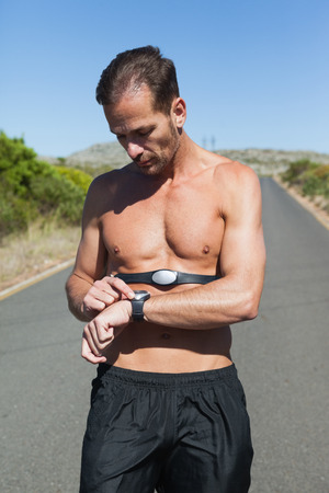 Athletic man on open road with monitor around chest on a sunny day photo
