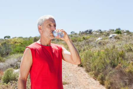 adventuring: Fit man drinking water on mountain trail on a sunny day