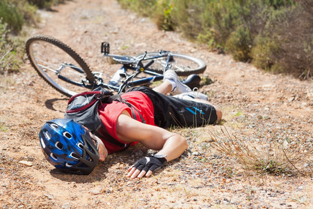 Injured cyclist lying on ground after a crash on a sunny day Stock Photo