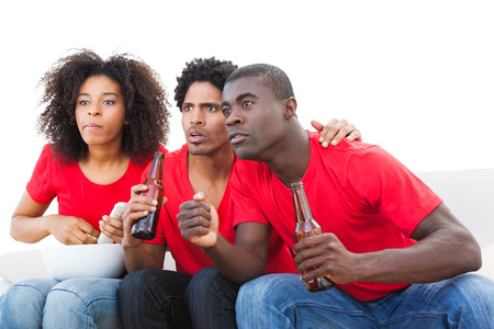 Nervous football fans in red on the sofa on white background photo