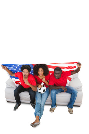 American football fans in red on the sofa on white background photo