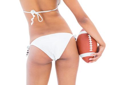 Fit girl in white bikini holding american football on white background photo