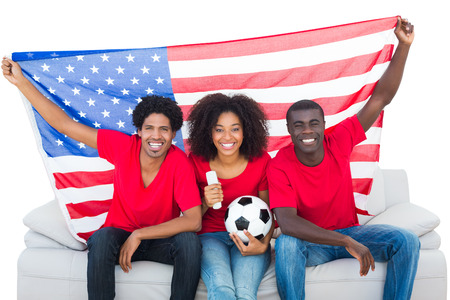 Happy football fans in red sitting on couch with usa flag on white background photo