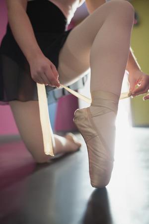 zapatillas ballet: Bailarina que ata la cinta en sus zapatillas de ballet en el estudio de ballet