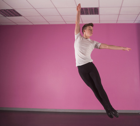 Focused male ballet dancer leaping up in the dance studio photo