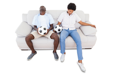 distraught: Distraught football fans sitting on the couch with balls on white background Stock Photo