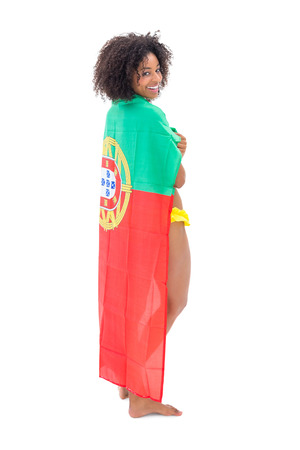 over shoulders: Smiling girl in yellow bikini holding portugal flag over shoulders on white background