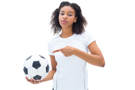 Pretty football fan in white holding ball and pointing to it on white background photo