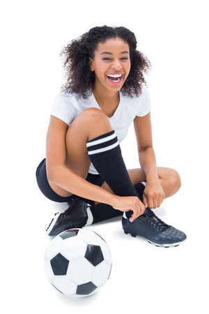 Pretty football player in white tying her shoelace on white background photo